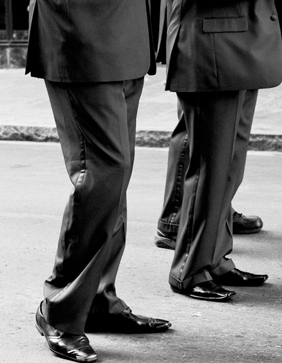 Business men wearing grey suits, and walking down the street.